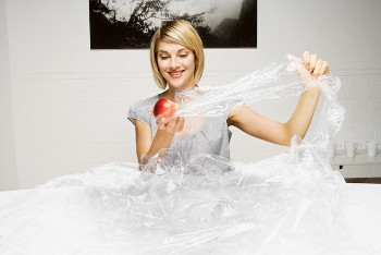 Woman Unwrapping Apple from Wasteful Amount of Cling Wrap --- Image by © Betsie Van der Meer/Corbis